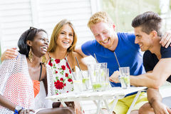 Happy young people laughing a being happy at a table Stock Image