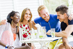 Happy young people laughing a being happy at a table Royalty Free Stock Photography