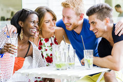 Happy young people laughing a being happy at a table Stock Images