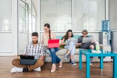 Young people sharing a collaborative office space in a modern hu. Happy young people laughing while sharing a collaborative office space as co-workers in a royalty free stock photography