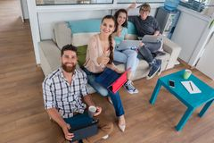 Young people sharing a collaborative office space in a modern hub. Happy young people laughing while sharing a collaborative office space as co-workers in a royalty free stock photography