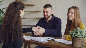 Young people are laughing and signing buy and sell contract then taking key and hugging during meeting with realtor. Happy young people are laughing and signing stock footage