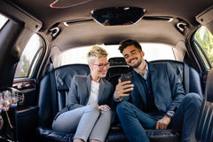 Happy young people in limousine. Watching smart phone and having laugh Royalty Free Stock Photography
