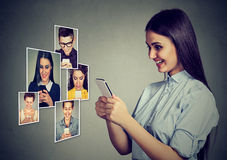 Happy young people men and women using mobile smart phone smiling. stock photo