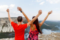 Happy young people among mountains Stock Image