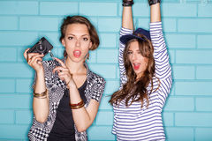 Happy young people with photo camera having fun in front of blue. Lifestyle portrait of two beautiful best friends hipster girls wearing stylish bright outfits Royalty Free Stock Photo