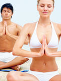 Happy young people practicing yoga at the beach Stock Image