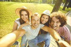 Happy young people selfie photos on the phone in the city park stock photography