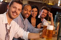 Happy young people sitting in pub, drinking beer. Portrait of happy young people sitting in pub, drinking beer, looking at camera, smiling Stock Photos