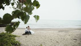 The bride and groom enjoy one another on the beach stock footage