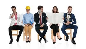 Happy young people sitting and waiting for a job interview stock images