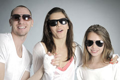Happy young people smiling. Beautiful white teens posing with sunglasses in studio Royalty Free Stock Photos