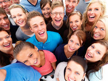 Happy young people standing in a crowd Royalty Free Stock Photos