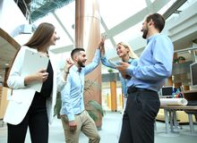 Happy young people standing in office and giving high five to their colleagues. Stock Photos