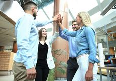 Happy young people standing in office and giving high five to their colleagues. stock photo
