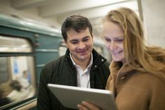 Happy young people with touch pad in subway royalty free stock photos
