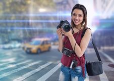 Happy young photographer on the city with flares and lights everywhere. Digital composite of happy young photographer on the city with flares and lights Royalty Free Stock Photos