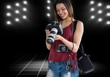 Happy young photographer looking the photos on the camera with stadium lights behind. Digital composite of happy young photographer looking the photos on the Stock Photos
