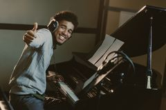 happy young piano player showing stock image