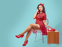 Happy Young Pinup Woman Sitting On A Chair And Talking On Phone Stock Image