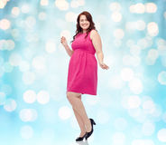 Happy young plus size woman dancing in pink dress Royalty Free Stock Images