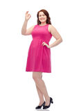 Happy young plus size woman posing in pink dress Royalty Free Stock Photography