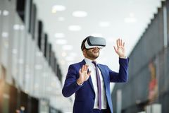 Virtual presentation. Happy young politics or businessman with vr headset expressing awe while watching conference Stock Images