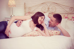 Happy young pregnant couple in bedroom Royalty Free Stock Images