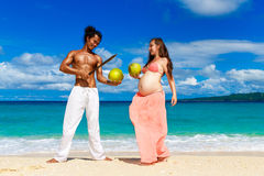 Happy and young pregnant couple with coconuts having fun on a tr Stock Images