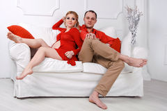 Happy young pregnant couple dressed in red embrace stock photography