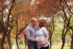 Happy and young pregnant couple embracing in nature Stock Photos