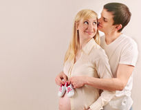 Happy young pregnant couple expecting a baby with little sneaker Stock Photo