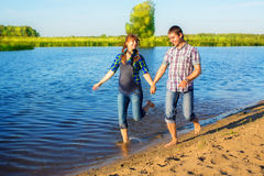 Happy and young pregnant couple having fun on the beach. Summer Stock Image