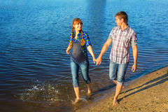 Happy and young pregnant couple having fun on the beach. Summer Stock Photos