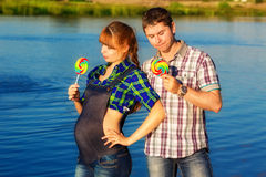 Happy and young pregnant couple having fun on the beach. Summer Royalty Free Stock Photo