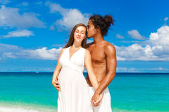 Happy and young pregnant couple having fun on a tropical beach. Stock Photos