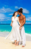 Happy and young pregnant couple having fun on a tropical beach. Stock Images