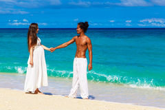 Happy and young pregnant couple having fun on a tropical beach. Royalty Free Stock Photography