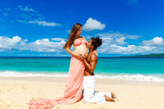 Happy and young pregnant couple having fun on a tropical beach. Royalty Free Stock Image