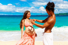 Happy and young pregnant couple having fun on a tropical beach. Royalty Free Stock Photos