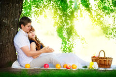 Happy and young pregnant couple hugging in nature enjoying summe Stock Images