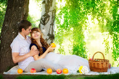 Happy and young pregnant couple hugging in nature enjoying summe Stock Image