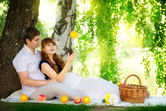 Happy and young pregnant couple hugging in nature enjoying summe Royalty Free Stock Images