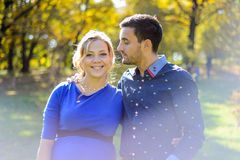 Happy and young pregnant couple hugging in nature royalty free stock photography