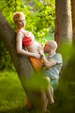 Happy and young pregnant couple hugging in nature Royalty Free Stock Photos