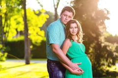 Happy and young pregnant couple hugging in nature Stock Images