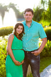 Happy and young pregnant couple hugging in nature Royalty Free Stock Photo