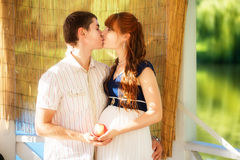 Happy and young pregnant couple hugging in the park. Summer vaca Stock Photo