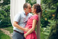 Happy and young pregnant couple in park in summer royalty free stock photos