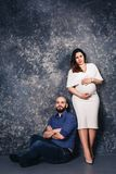 The happy young pregnant couple in the studio on a dark background. family relationship concept. royalty free stock photo